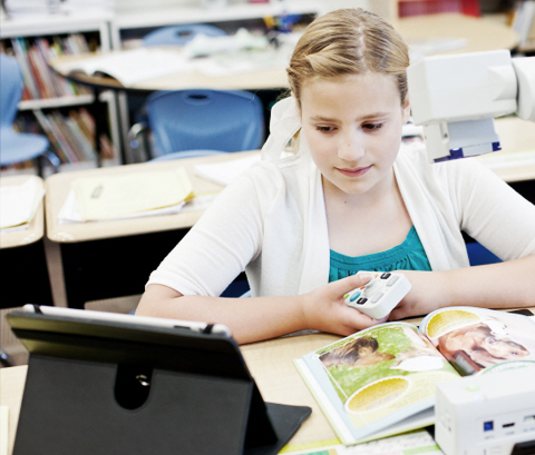 Girl reading a book with an iPad and assistive technology.