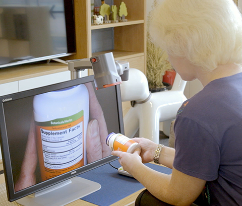 Woman looking at prescription medication with the Go Vision magnifier.